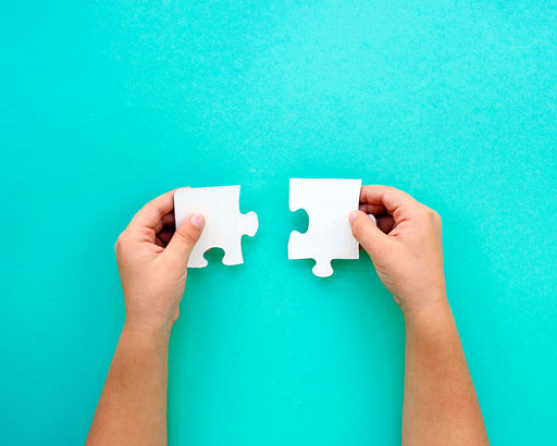 Person's Hand About to Put Puzzle Pieces Together